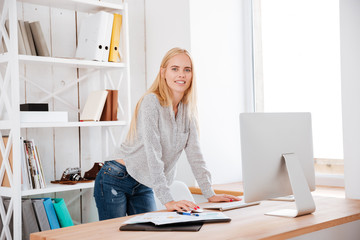 Happy attractive business woman standing and working with computer