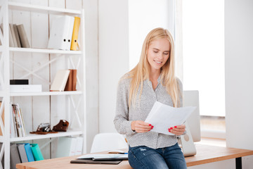 Smiling businesswoman sitting on the office desk and reading documents