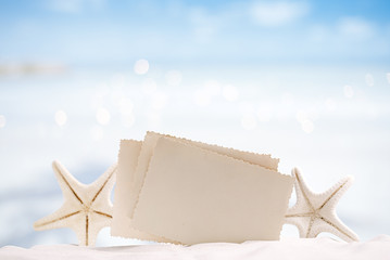 white starfish with blank retro photo on white sand beach, sky a