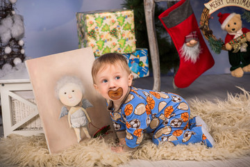 Christmas morning, baby in sleepwear with dummy near gift boxes, picture with x-mas angel and near christmas stockings