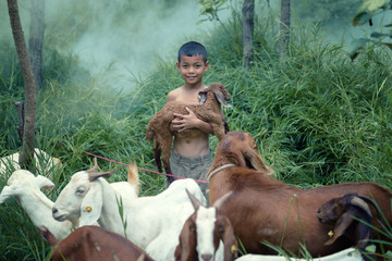 asia young man carrying a sheep in a forest area with.Wear tradi