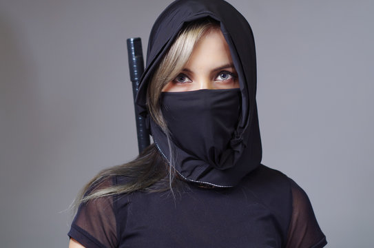 Samurai woman dressed in black with matching veil covering face, sword hidden behind back, facing camera, ninja concept