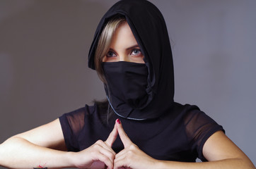 Headshot samurai woman dressed in black with matching veil covering face, resting arms on desk and touching fingertips against each other, facing camera, ninja concept