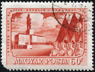 Stamp printed in Hungary shows May Day demonstration in Budapest against the backdrop of the monument to Joseph Stalin