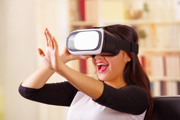 Young brunette woman wearing virtual reality goggles experiencing future technology, interacting and smiling while playing, domestic background,vr concept