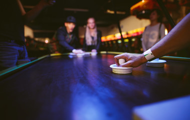 Young friends playing air hockey game