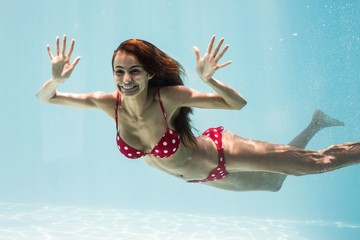 Cheerful young woman swimming