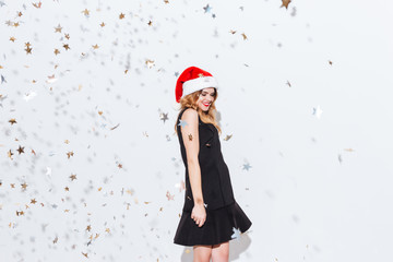 Smiling cute young woman in santa claus hat standing