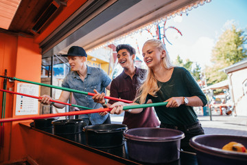 Friends having fun with fishing game in amusement park