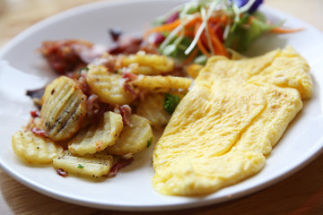 A delicious home style breakfast with crispy bacon, eggs omelett
