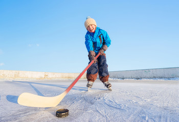 Winter games. Young happy child playing ice hockey on an outdoor ice rink. Focus on the boy.