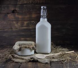 бутылка молока и банка сметаны с деревянной ложкой