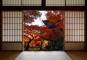 Ancient pagoda and beautiful red fall maples seen through a traditional Japanese doorway in autumn