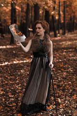 Young attractive woman standing in fall park and holding burning musical notes in hand, leaning on cane