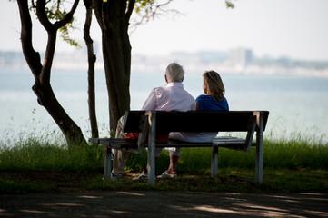 Paar auf einer Bank am Wanderweg an der Küste