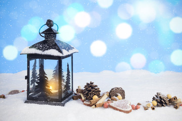 Christmas decoration with lighted candle lamp and pines, white snow and blue background with copyspace.