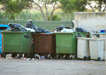 Full garbage bins on the street.