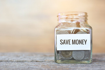 "Money in a glass jar with ""save money"" word. concept siphons money"