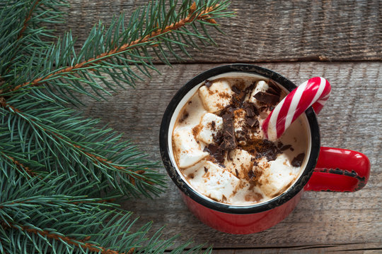 Christmas drink. Hot chocolate with marshmallows and candy cane on the wooden background. Hot cocoa with marshmallows. New Year. Holiday card. Rustic style. Close up.