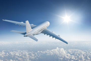 Big plane flying towards with the sun in blue sky Wall mural