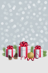 Christmas gift boxes wirh decorations and fir branches on silver bokeh background vertical composition