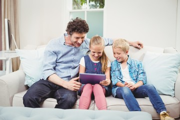 Father with children using digital tablet on sofa