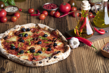 Delicious, tasty and fresh, rustic Italian pizza, served on wooden table. Bunch of tomatoes, chili, basil, garlic in background. Bowls with different kinds of pepper. Many bottles of olive oil