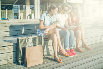 Summer sunny day, three young women resting after shopping sitting outdoors.In hands of girls smartphones and tablet computer.Nearby are brown and black shopping bags.Girls showing pictures on gadget.