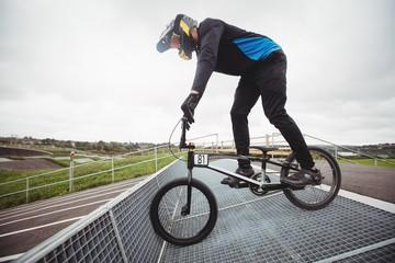 Cyclist preparing for BMX racing at starting ramp