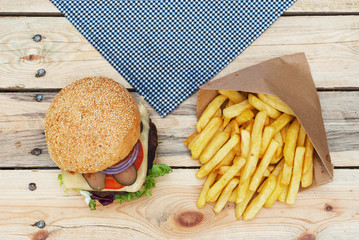 Grilled beef burger and french fries on wooden table - top view