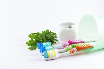 Toothbrushes and dental floss on white background