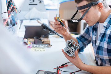Young man repairing drones chip with a screwdriver