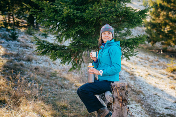 Woman in bright sport clothes is drinking a delicious tea while