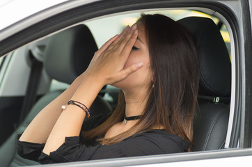 Closeup young woman sitting in car interacting upset frustrated, covering face in hands, as seen from outside drivers window, female driver concept