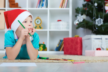 Little boy in Santa red hat going to paint. Christmas concept..