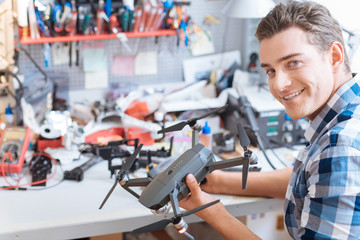 Joyful man holding drone propeller and remore controller