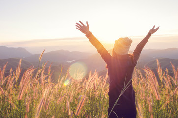 Carefree Happy Woman Enjoying Nature on grass meadow on top of mountain cliff with sunrise. Beauty Girl Outdoor. Freedom concept. Len flare effect. Sunbeams. Enjoyment. Fototapete