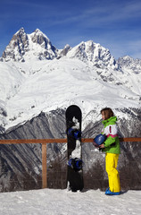 Young snowboarder with helmet in hands and snowboard on viewpoin