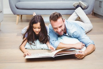 Father and daughter looking in picture book on floor