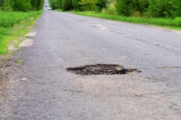 dangerous pothole in the asphalt highway, summer