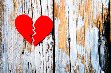 Paper broken heart on white wooden background. Copyspace