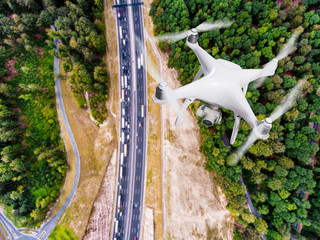Hovering drone taking pictures of highway in forest, Netherlands