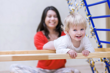 Young mother with happy baby boy doing exercises