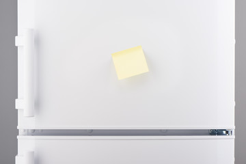 Blank light yellow sticky paper note on white refrigerator