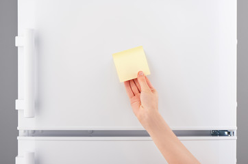 Hand holding yellow sticky paper note on white refrigerator