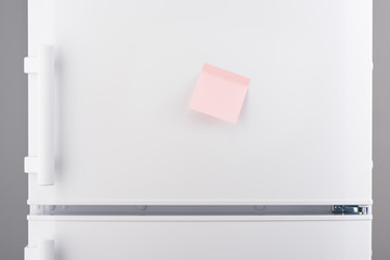 Blank light pink sticky paper note on white refrigerator