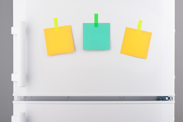 Blank green and yellow paper notes attached on refrigerator