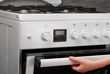 Female hand opening oven in white kitchen gas stove