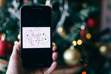 person takes a photo on a smartphone of HAPPY NEW YEAR with a christmas background