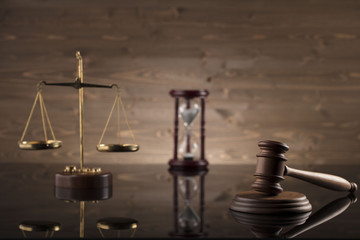 law theme, mallet of the judge, justice scale, hourglass, books, wooden background